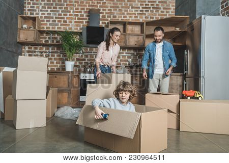 Happy Parents Packing Boxes And Son Playing With Toy Car While Relocating