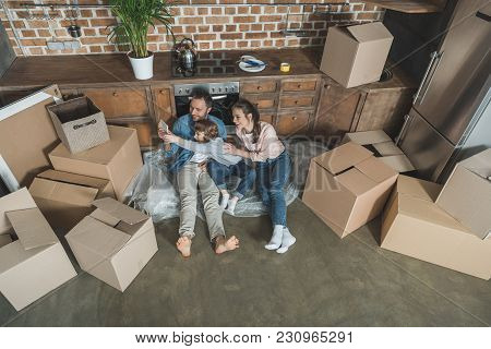 High Angle View Of Happy Family Taking Selfie With Smartphone While Relocating