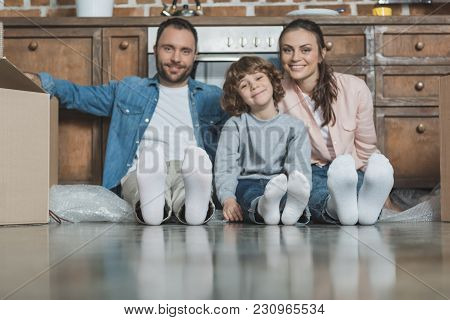 Happy Family With One Child Smiling At Camera While Sitting On Floor During Relocation