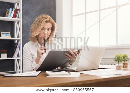 Thoughtful Successful Businesswoman In Formal Wear Sitting At Wooden Desk In Modern Office And Readi