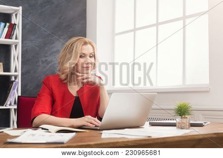 Concentrated Businesswoman Working On Laptop At Office. Businesswoman Typing Something On Computer W