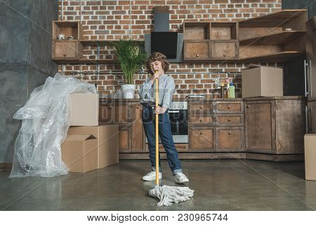 Little Boy Having Fun With Mop While Cleaning New Apartment After Relocation