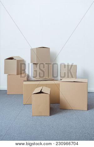 Stacked Cardboard Boxes In Empty Room During Relocation