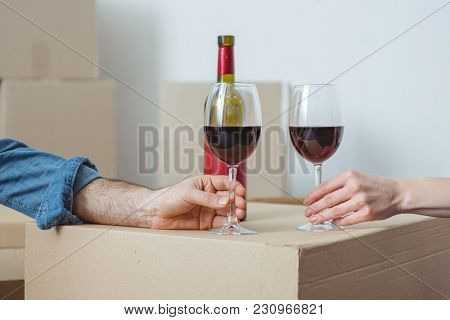 Partial View Of Couple Holding Glasses Of Wine And Celebrating Relocation