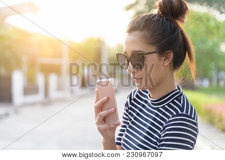 A Beautiful Woman With Has Playing Phone And Selfie In The Evening With Sunset Time At Garden Park A