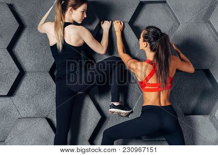 Fit Women Posing Like A Climber Hanging On Decorative Wall.