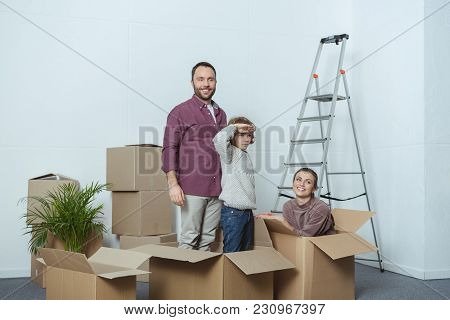 Happy Family With One Child Having Fun With Cardboard Boxes During Relocation