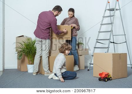 Parents Packing Boxes And Son Playing On Floor During Relocation