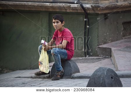 Istanbul Turkey 05 July 2017 A Boy Selling Paper Napkins Sitting On A Stone On The Street