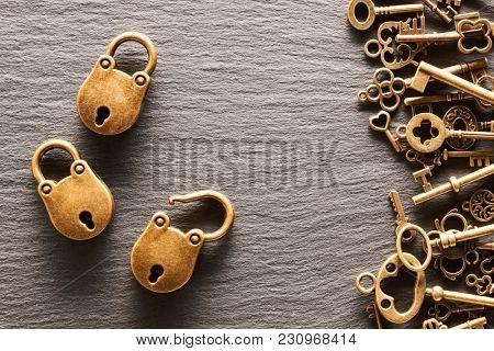Various metal keys and locks over slate background