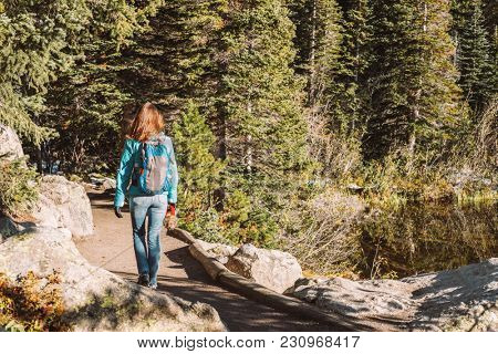 Woman tourist walking on trail near Bear Lake at autumn in Rocky Mountain National Park. Colorado, USA.