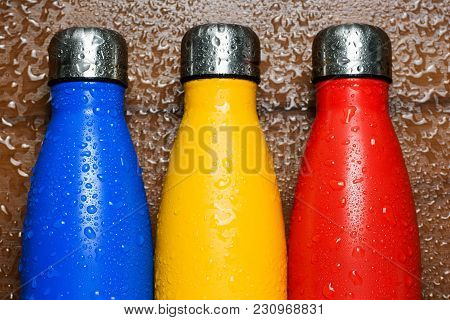 Colorful Stainless Thermos Bottles On A Wooden Table Sprayed With Water