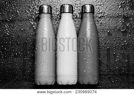 Stainless Thermos Bottles On A Wooden Table Sprayed With Water. Black And White