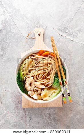 Asian Noodles In Broth With White Fish, Bok Choy  In Bamboo Wooden Tray On Grey Background