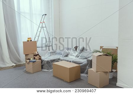 Stacked Cardboard Boxes, Ladder And Toys In Empty Room During Relocation
