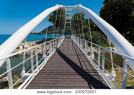White Metallic Bridge With Wooden Floor For Pedestrians Near The Sea At The Agios Ioannis Village, A