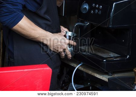 Barista using coffee machine to Steaming milk froth for preparing coffee. Microfoam is milk formed using a steam wand on an espresso machine. poster