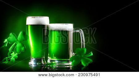 St. Patrick's Day Green Beer pint over dark background, decorated with shamrock leaves. Patrick Day pub party, celebrating. Glass and Mug of Green beer close-up. Border art design, Wide format banner