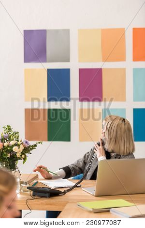 Magazine Editor Talking On Phone And Looking At Color Palette On Wall