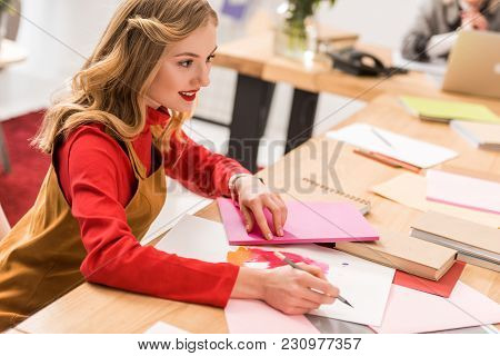 Smiling Magazine Editor Working With Sketches And Documents In Modern Office