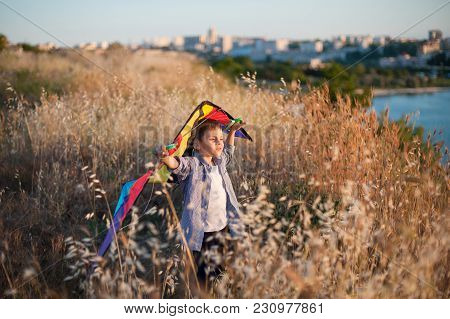 Handsome Little Kid Holding Colorful Kite Standing Among Grass Field Near Sea With Town