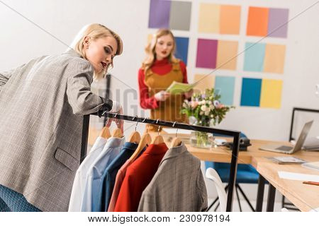 Fashionable Magazine Editors Working With Clothes In Modern Office