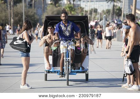 Barcelona, Spain - July 31, 2016: Young Rickshaw Gives A Lift To Cheerful Tourists Along The Beach I