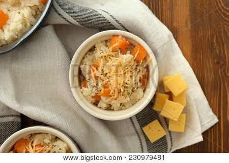 Bowls with delicious pumpkin risotto on wooden table