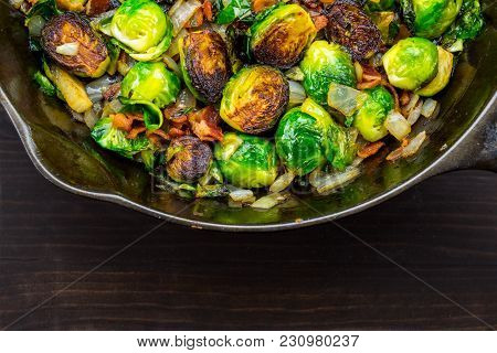 Wide Half View Of Roasted Brussels Sprouts And Bacon In Cast Iron Skillet