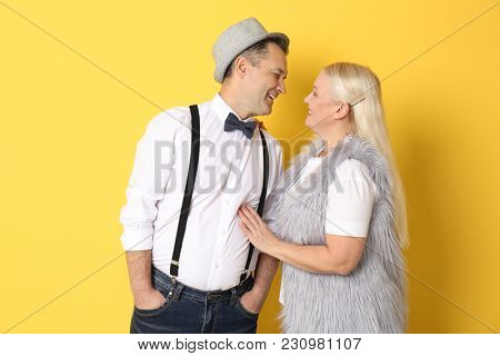 Portrait of stylish pensioners on color background