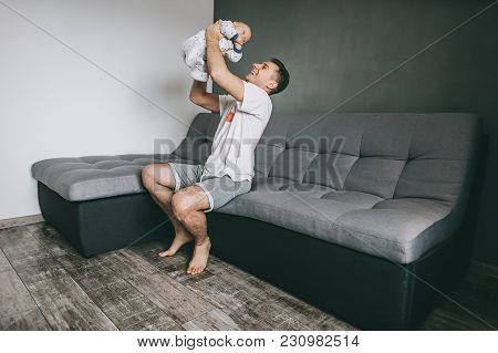 Happy Young Father Sitting On Sofa And Playing With Cute Infant Child