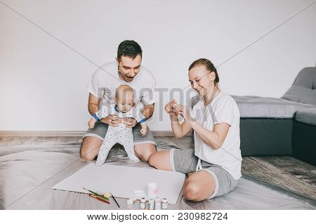 Beautiful Happy Young Family With Adorable Little Infant Child Painting Together On Floor At Home