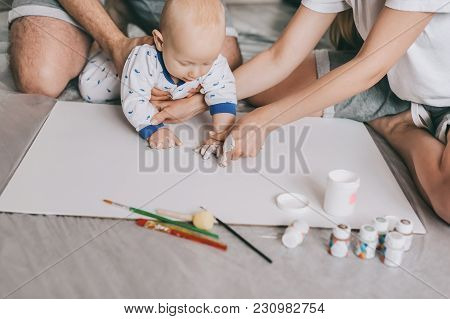 Cropped Shot Of Young Family With Beautiful Infant Child Painting Together On Floor