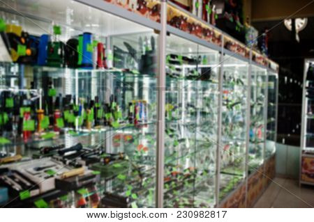 Blur Photo Of Shelves Store Weapons On Shop Center.