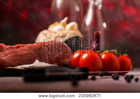 Detail Of Red Tomatoes Next To Pork Tenderloin On Wooden Board