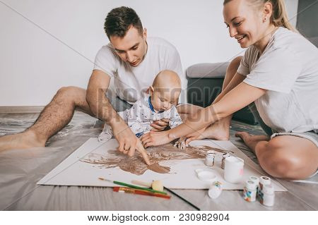 Happy Young Family With Cute Little Child Painting Together On Floor At Home