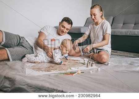 Young Family With Adorable Infant Child Painting Together On Floor