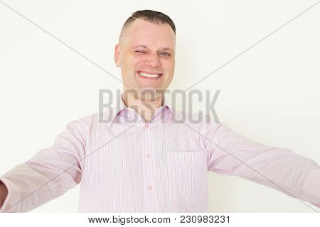 Portrait Of Mid Adult Caucasian Businessman Wearing Striped Shirt Taking Selfie And Smiling At Camer