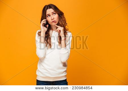 Pensive confused brunette woman in sweater talking by smartphone and looking away over yellow background