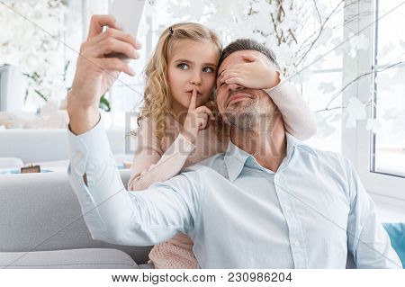 Daughter Covering Eyes Of Father And Showing Silence Sign While They Taking Selfie