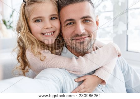 Father And Daughter Embracing And Takig Selfie