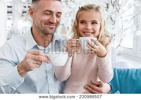 Young Father And Daughter Drinking Tea In Cafe