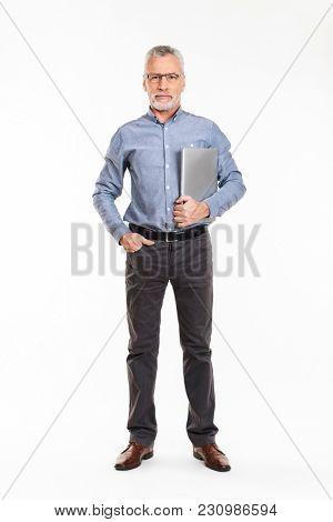 Confident mature man in eyeglasses holding laptop computer and looking camera seriously isolated over white
