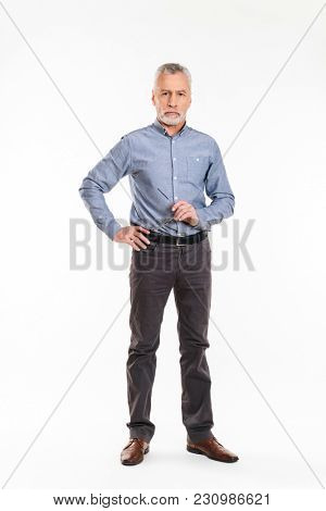 Full-length shot of old grey-haired man looking camera seriously and holding eyeglasses isolated