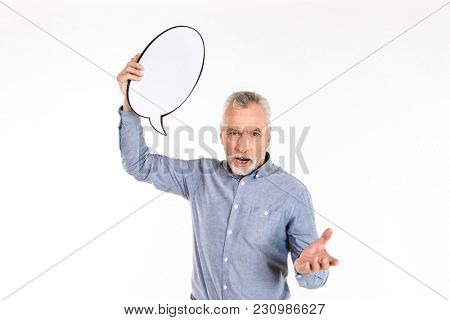 Displeased old man holding blank bubble speech and screaming to camera angry isolated
