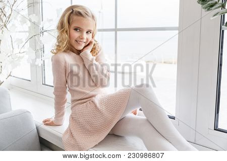 Stylish Little Child In Pink Dress Sitting On Windowsill