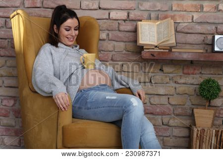 Happy pregnant woman at home relaxing in armchair holding cup of tea.