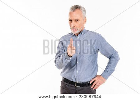 Serious confident mature man pointing at you with finger isolated over white