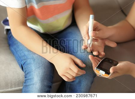 Woman and her diabetic son with lancet pen and glucometer taking blood sample at home, closeup