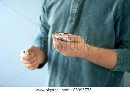 Diabetic man with digital glucometer and lancet pen on color background, closeup